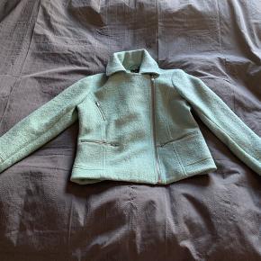 Lækker mintgrøn jakke i bikerstil str 44 (UK 16). Aldrig brugt. 60% polyester, 40% uld. Måler 45 cm over skuldrene. Brystmål er  2 x 55 cm. Længden er 60 cm.