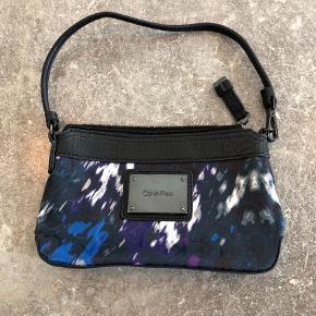 Varetype: Håndtaske Størrelse: 13x21 Farve: Sort Oprindelig købspris: 699 kr. Prisen angivet er inklusiv forsendelse.  Calvin Klein taske som også kan bruges som clutch (uden hank/rem) sælges. Ubrugt og fremstår helt som ny. Sælges til højeste bud, sat til salg på flere  sider.
