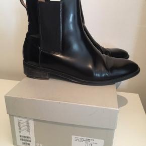 Sorte Chelsea støvler i lak/læder  De har en ridse på indersiden af begge støvler, kan ses på billede 2