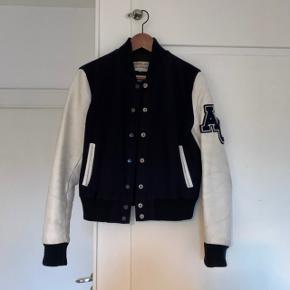 Flot baseball jakke fra American College. Fitter lille i størrelsen. Står til en str. L men passes af en S-M  Mørkeblå med hvide læderærmer