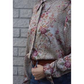 Silkeskjorte fra 1970'erne i perfekt stand fra Barcelona. Skjorten har et meget flot mønster med blomster og tekst. Den klæder jeans enormt meget, men kan også kombineres med andet. Har et virkelig lækker stof. Passer størrelse 34-40. Kan også kombineres med et bælte i midten. Pris: 200 kroner. Skriv en privat besked for mere info 🌸