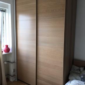 Rummeligt garderobeskab med skydedøre. Skabet er designet så man kan rykke rundt på hylderne, alt efter hvordan man foretrækker fordelingen af pladsen i skabet. Fx kan man i den ene side af skabet have plads til at hænge tøj på bøjler og den anden side have skuffer og hylder.  Højde: 236,5 cm Dybde: hylder: 57,5 cm skab med dør: 60 cm Bredde: 150 cm Vi vil gerne hjælpe med, at skille det ad, så det er nemmere at tranportere.