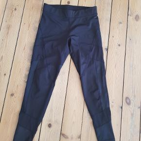 Lækre sorte træningstights med mesh-paneler på benene (der er en stribe mesh i siden midt på låret og en lidt over anklen). Brugt meget få gange, så er som nye.