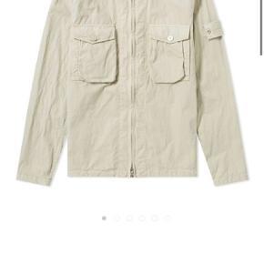 """Jeg sælger hermed min meget fine overshirt fra Stone Island Ghost. Overshirten er aldrig brugt, hvilket betyder at den fremstår som ny. Størrelsen på overshirten er en Large, og den har et """"normalt"""" fit."""