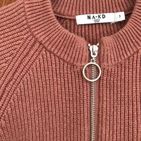 Strikket half-zip trøje i støvet rosa/brændt laks. Trøjen er brugt 2 gange og fremstår derfor som ny.