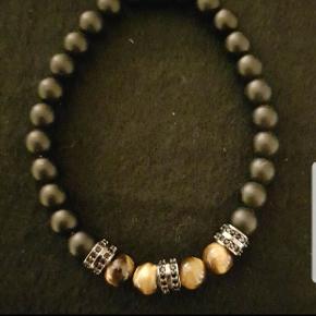 Rigtig flot armlænke armbånd af sorte perler og antik sølv. Er elastisk og kan tilpasses dit håndled.