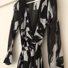 Lang kjole. Underdelen er lidt plisseret. Bindes i den ene side.