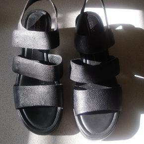 Virkelig lækre plateau sandaler Sort læder og foret med skind. Indersålen er let polstret, hvilket gør sandalerne yderst behagelige. Kun brugt 1 gang i et par timer. De er super behagelige at gå i for min venstre fod😉, men ikke for den højre idet sandalen trykker på min knyst... Øv! De 2 øverste remme er justerbare.   Str. Hedder 37, men svarer mere til 37,5. Indvendigt måler 👡 24 cm i længden.  Hæl højde er 6.5 cm. Plateau 2 cm.   BYTTER IKKE!  SÆLGES TIL PRISEN!