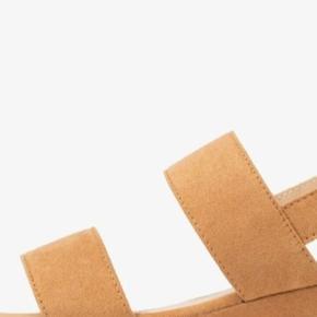 MTNG sandaler fra Zalando, nye aldrig brugt. MATERIALE  Udvendigt materiale: Tekstil For: Imiteret læder Sål: Læder Sål: Kunststof Foring: Meget let foring Materialets detaljer: Imiteret læder INFORMATION OM PRODUKTET Skospids: Åben Hæl: Kilehæl / wedge, plateau forrest Lukning, lås: Spænde/sløjfe