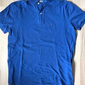 Blå polo fra Tommy Hilfiger. Størrelse small. Kan sendes eller afhentes i Halsnæs omegn.
