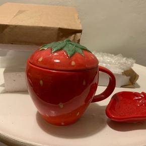 Rød jordbær krus / kop med låg og lille jordbær asiet til evt the brev eller til mini petit four.  Højde på kop / krus knap 9 cm og længde på mini asiet ca 9 cm. Nypris for kop/krus 135 og for mini asiet 70 Sælges for 99,- pr sæt! (Har 4-6 sæt indpakkede sæt)