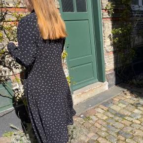 Denne flotte sorte kjole med små hvide blomster og lange ærmer, er så fin at have på. Den er super flot også med et bælte i taljen. Den kan knappes op så man får en lille slids foran, hvilket giver et ungt og sexet look. Kjolen sælges desværre da den ikke bliver gået med.