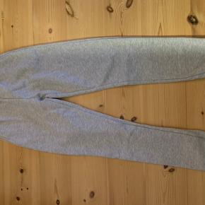 Helt nye lysegrå Joggingbukser fra Nelly Trend. Aldrig brugt og aldrig været i vask - står som helt nye. (Fejlkøb) Elastik i ben og øverst i buksekanten.  Fragt betales af køber (48,-)
