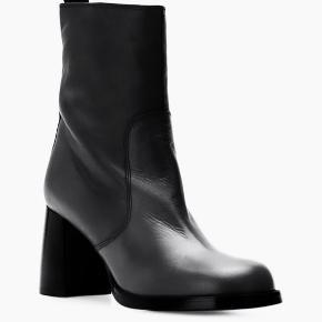 Sorte støvler med lynlås i siden fra Joseph med en mandeltå, en trækflip bagpå og en midthøj blokhæl.