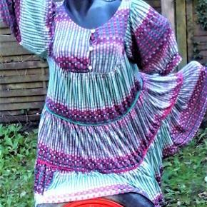 Brand: Fantastisk stof design Varetype: kjole - Inspiration etniske klæder Størrelse: M/L Farve: Multi  Smukt stof , smuk kjole i viskose og kunst . Dens stærke side er det flotte stof . Måler ca 48 x 2 = 96 cm i brystvidde ( målt uden rynk , hvilket gør størrelse flexsibel ) . Længde ca 78 cm. Ærmer ca 30 cm . Har bærestykke for og bag uden ryng . påsat 3 baner med rynk . Knaplukning foran .