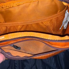 Unisex fanny bag i orange/bordeaux. Kan både bruges som crossbody eller i taljen.
