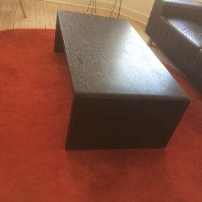 Sofabord - sort finér. Længde: 125 cm, højde: 40 cm. Farven er delvist slidt af, så måske bordet skal males i en ny farve hos dig :)