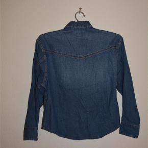 Varetype: skjorte Farve: Blå  Denim Skjorte fra Wrangler  Str. Medium 66 cm fra nakke og ned. 54 cm fra skuldersyning og til ærme afslutning. 50 cm fra skulder syning til skulder syning  som afbillede
