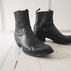 Lædersmedens Beatlesstøvle er smedens egen udgave af de støvler, som The Beatles brugte i deres første år. Lædersmedens støvler er dog rendsyet i modsætning til de originale, som er limet. Denne smukke støvle er blevet meget populær, især blandt musikere.  Skocreme medfølger.  Støvlerne er kun brugt et halvt års tid, hvorefter de har stået stille i skabet i et par år. Har stadig mange år i sig endnu.  (Ny pris: 2100)