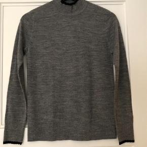Varetype: Rullekrave Farve: Grå Oprindelig købspris: 700 kr.  Fin merino uld bluse, med fin sort kant.  Bytter ikke.  Mp. 200,- pp