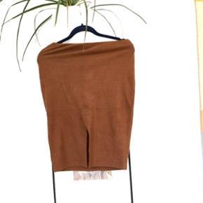 Nederdel i imiteret ruskind med slids foran. Kontor look. Sidder super godt med elastik i stoffet og i kanten. Brugt een gang, derfor som ny.  Mærke: Atmosphere. Str. 38