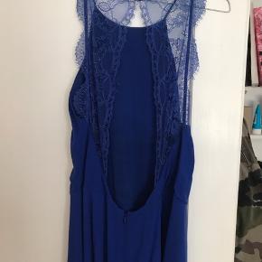 En smuk blå kjole med bar ryg. Den lukkes med lynlås til lænden. Den falder smukt foran ved barmen.