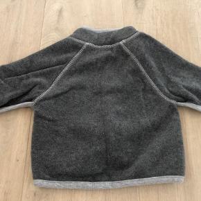 """Molo fleecetrøje i mørk grå med små sølv """"luffer"""" som lommer foran. Syningerne er med sølvtråd. Rigtig lækker blød jakke.  Fra dyre- og røgfrit hjem. Sender gerne. Prisen er plus evt. porto."""
