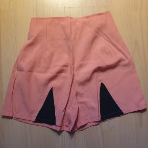 Højtaljede og figursyede shorts med lynlås. Bleg pink i farven. Elastik på bagsiden.