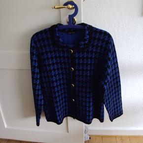 Velholdt strikcardigan/ jakke i uld/ polyester. Mangler størrelsesmærke - se mål: Brystvidde ca. 53cm x 2 - samme bredde hele vejen ned. Længde ca. 63 cm. Sendes fragtfrit i uge 42