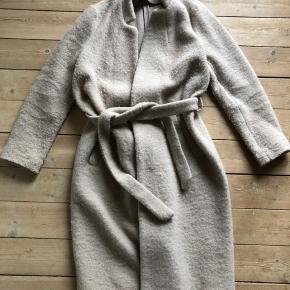 Sandfarvet uld-frakke med bindebælte. Jeg har brugt den ifbm graviditet da den kan følge en voksende mave   Sender ikke