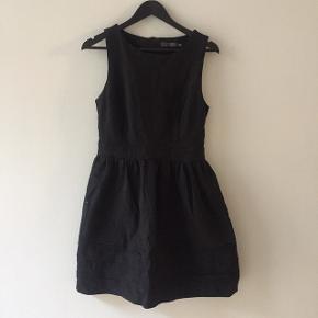 """Fin, sort kjole i tykt stof med """"strut"""" fra taljen og ned. Går til midt på låret."""