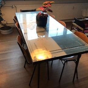 Snedkerlavet bordplade af fyldningsdøre. Den har en ramme af sort stål, der er behandlet med bivoks, og en hærdet glasplade, der dækker hele bordpladen.  Stellet medfølger ikke. Kun bordpladen sælges.  Mål: B: 90cm L: 200cm