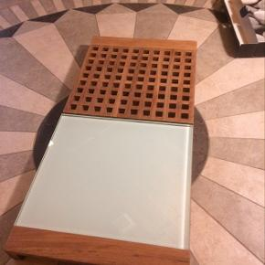 Trip Trap bakke tapas bordskånere, Trip Trap  Super anvendeligt og pladsbesparende.  Her har du en alt-i-en løsning fra Trip Trap.  Det er et kombineret produkt bestående af en dyb bakke med håndtag, og ovenpå er der to seprarate firkanter - den ene i glas og den anden i Trip Traps karakteristiskte tern. Der er dutter nedenunder, så de kan stilles ved siden af på et bord og bruges til fx. bordskånere til varme ting  En god størrelse, som kan stå midt på bordet, til en hyggelig middag mål: 49 x 24 cm.  Kan bruges samlet som fx. tapasbræt med glasdelen til ost og den anden som til brød. Meget anvendeligt.  Original emballage medfølger.  Befinder sig i Aalborg, men sender gerne