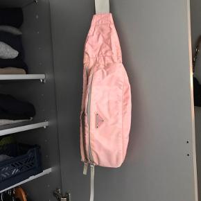 Sælger denne Prada Crossbody bælte taske i en pink farve. Den er købt på vestaire collective sidste år, så der medfølger ægtehedsbevis derfra. Den er brugt, og har lidt brugsspor i kanterne, men ellers er den i rigtig fin stand