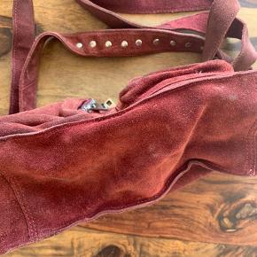 """Bordeaux ruskindstaske fra Nunoo. Har tegn på slid i bunden i form af lidt """"pletter"""" og på bagsiden og foran i form af slid på ruskindet. Remmene har også tegn på slid i form af lidt affarvning af farven."""