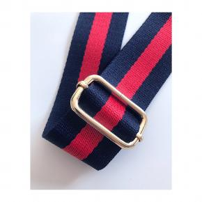 Justerbar taskerem / skulderstrop, som både kan bruges til skuldertasker og Crossbody-tasker. Farven på selve stroppen er rød og mørkeblå. Stand ny og endnu ikke taget i brug.   Mp: Se prisen + evt. porto  Tag også gerne et kig på mine mange andre annoncer.