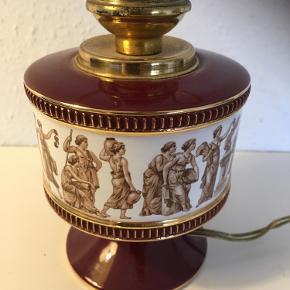 Gl finere lampe med græske mytologier ? I frise   Lampefod i bordeaux porcelæn med guldkanter og metal   Skal have ny Ledning og evt lampeskærm eller glødepære   Ca 35-40 cm høj   Fin stand.  Unika   Sender gerne   Se flere annoncer