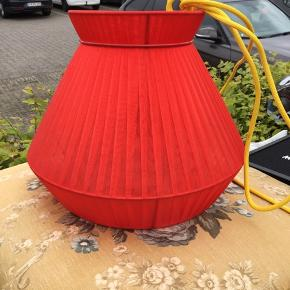 Rød loftslampe med gul stofledning fra nud.