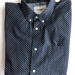 Carhartt skjorte i navyblå med små hvide prikker. Brystlomme og lange ærmer.  Str.: L Materiale: 100% bomuld.  Brugt få gange. Nypris ca. 499 kr.