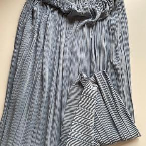 Plisseret nederdel i fineste shiny lyseblå.  Passer en str. m/l Jeg er 173 cm og den går mig til midt på skinnebenet