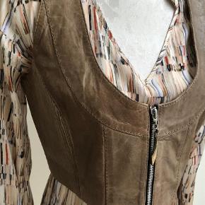 Varetype: Vest Farve: Camel  Lækker skindvest med flotte detaljer. Passer til en tilsvarende jakke, som jeg også har til salg. Har aldrig været brugt.
