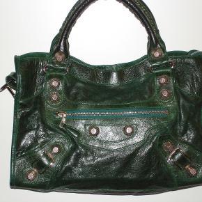 Fantastisk Balenciaga City GHW Emerald Green taske SOM NY. Størrelse 36 X 26 X 13 cm. Balenciaga City  med Giant Hardware i Silver med hanke og skulderrem (ikke velegnet som crossbody) i den skønneste grøn-sorte farve kaldet Emerald Green. Den er usædvanlig smuk og andreledes unik end den traditionelle sorte, men stadig meget mørk. Skindet er så smukt med en fantastisk glans. Tasken fremstår ny og bærer ingen spor af brug. Jeg har købt den her på Trendsales, og den har været brugt til en modeopvisning. Derfor følger der ingen kvittering med tasken. Føl dig fri til at få tasken verificeret på Purseforum, men jeg garanterer ægtheden. Jeg har tilføjet de fotos, der bruges til at verificere en Balenciagas ægthed. Dette er den 8. Balenciaga taske, jeg har ejet. De er rene kunstværker og samleobjekter. Denne taske fremstilles ikke længere med Giant Hardware, så tasken er virkelig noget særligt og virkelig et samleobjekt. En Balenciaga City med Small Hardware koster i Illum 11.600 kroner. Denne taske med Giant Hardware er væsentligt dyrere. jeg sælger den for 8.300 kroner. BYTTER IKKE!