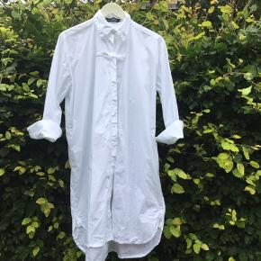 Spritny oversize & lang hvid Ivan Grundahl skjorte i str S i 100% bomuld ( mærke desværre faldet af). Den har en smart lukketalje foran ved stolpelukningen. Skjorten er længere bagpå. Ubrugt, ingen pletter el andet  Skjortens brystmål er ca 60 cm x 2 Nypris 1899 Sælges for kr 650 excl forsendelse