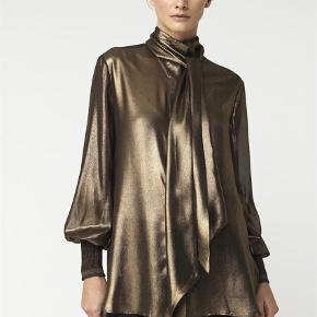 """Varetype: Langærmet Farve: Gylden Oprindelig købspris: 2000 kr.  Super fin skjorte med """"pussy bow"""" kan knappes af og bruges uden. Fine strik detalje ved ærmerne. Str. 36, aldrig brugt, stadig tag på ny pris 2000 kr. Bytter ikke - mp. 1100 kr pp. via mobilepay  Brystmål 53 x 2 - længde målt bagpå 77 cm, lidt kortere foran."""