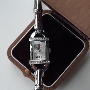 Smukt Diamant ur fra GUCCI med original GUCCI urlænke sælges.  Model 6800L.  Prydet med 26 brillant slebne diamanter. Uret er ekstremt velholdt. Certifikat, original boks, original yderboks samt ekstra led til ur-lænken medfølger.  Vejl. nypris 16.200,- kr.  ** Gucci - Ur med diamanter - Diamant - Damearmbåndsur - Dameur - Smykkeur **
