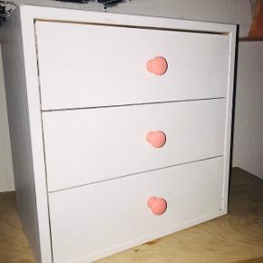 Fin lille reol med 3 skuffer til eksempelvis børneværelset.   Den er lavet i træ og malet med hvid/rosa maling.  Den kan hænges op, og vi har brugt den til tuscher, perler m.m. på vores datters værelse, men kan også bruges som natbord.  B: 30 cm H: 30 cm D: 19 cm