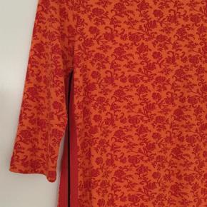 Varetype: Kort Farve: Orange,Rød  Meget sød og anvendelig kjole i lækkert stof med trekvarte ærmer . Sjovt bånd påsat i begge sider af kjolen  i orange og med sort stribe. Str M Farven orange over i let rødlig / flot  Bryst ca 47 x 2 cm og hoftevidde ca 51 x 2 cm. Stof står ikke i kjolen, men er polyester med elastan.