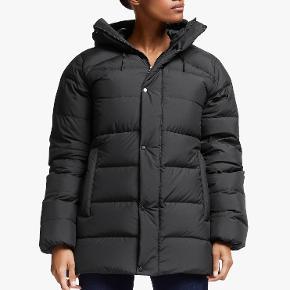Dynejakke, str. 38, haglöfs, sort, Ubrugt Style: Haglöfs Näs Down Jacket En supervarm outdoor jakke med design, funktion, slidstyrke og gennemtænkte detaljer fra frilufts mærket Haglöfs.  En blanding af let materiale gør jakken både varm og let at pakke ned. Fluorkarbonfri, DWR-behandlet, vand- og snavsafvisende overflade. Fyldningsgrad 700 CUIN dun af premium kvalitet med fluorkarbonfri DWR-behandling kombineret med QuadFusion™-materiale i skuldre og vindslåer. To-vejs justerbar hætte for behagelig beskyttelse mod vejr og vind og en varmende, tætsiddende pasform. Lynlås med ydre vindslå med trykknapper. To håndlommer med lynlås. Elastiske ærmeender. Ryglængde midten 78,3 cm (damestørrelse M) For: Fyldningsgrad 700 CUIN 85 % dun/15 % fjer af premium kvalitet, behandlet med fluorkarbonfri DWR for at beholde sin høje funktionsevne i fugtigt vejr og for at forkorte tørretiden.  NYPRIS: 3000 ,- Jakken er aldrig brugt og har stadig prismærke på.