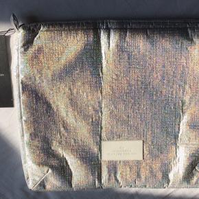 Clutch i sølv metal look, med lynlås og hvidt for. Aldrig brugt, originalt mærke sidder stadig på.  Mål: 30x36x3 cm.  Sender gerne flere billeder, da der kun kan vises 3 herinde.   Kan afhentes i Køge (evt. Roskilde station) eller sendes, Køber betaler fragtomkostninger.