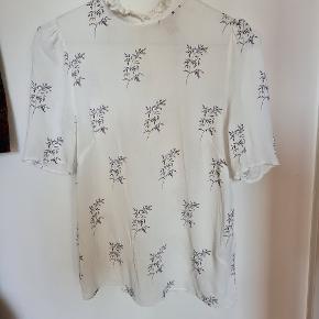 Sød bluse med korte ærmer fra h&m trend. Grøn og lilla blomst detaljer og kort flæse i hals udskæringen